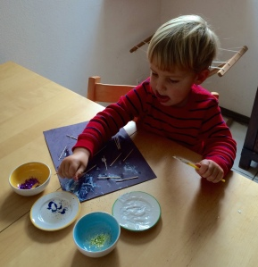 Zachary (2yr 11mo) concentrates while learning to glue toothpicks and glitter.