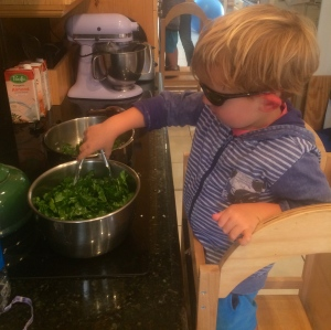 Transferring chopped chard from a bowl to the pan with tongs.